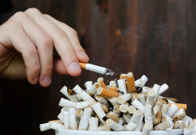 A man taps ashes off his cigarette into an ashtray filled with cigarette butts on a table in Ljubljana